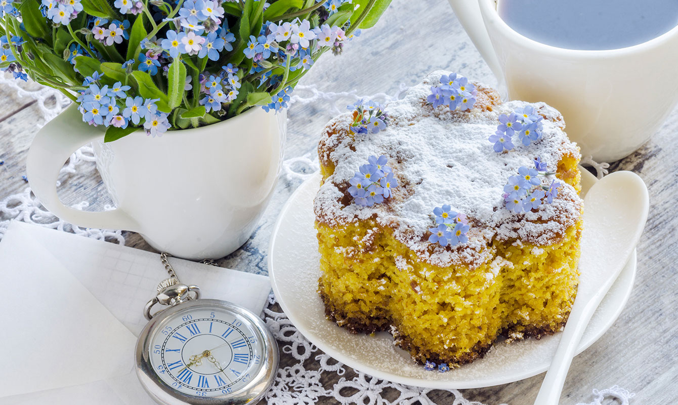 Ätbar blomma av förgätmigej som dekoration på en kaka