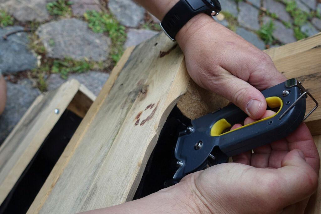 Använd häftpistolen för att fästa markduken i lastpallens innerkant.